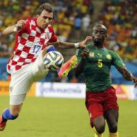 Two for Mario: Croatia's Mario Mandzukic (left) vies for the ball with Cameroon's Dany Nounkeu in Manaus, Brazil, on Wednesday night. Croatia routed Cameroon 4-0. | REUTERS