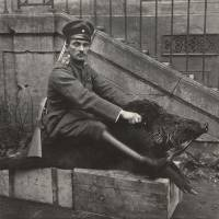A German Air Force officer sits astride a dead boar outside a house near to where he was stationed on the Western Front in 1918. | REUTERS