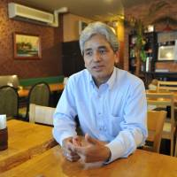 Halfway house: Democracy campaigner Kyaw Kyaw Soe speaks at Ruby, the restaurant he runs with his wife, Nwe Nwe Kyaw, in Takadanobaba, Tokyo. | YOSHIAKI MIURA