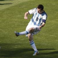 Lethal weapon: Argentina's Lionel Messi (right) shoots past Iran's Reza Ghoochannejhad to score the winning goal in Saturday's 1-0 victory. | AFP-JIJI