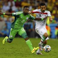 Stalemate: Nigeria's Ogenyi Onazi vies for the ball with Iran's Reza Ghoochannejhad on Monday in Curitiba, Brazil, on Monday. The match ended in a scoreless draw. | REUTERS