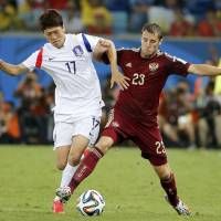 Honors even: South Korea's Lee Chung-yong (left) and Russia's Dmitry Kombarov compete for the ball on Tuesday. | REUTERS