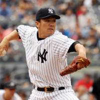 Wins again: Masahiro Tanaka fires a pitch against Oakland in the first inning on Thursday. The Yankees edged the A's 2-1.   REUTERS