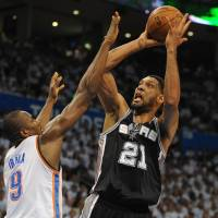 Powerful force: San Antonio's Tim Duncan shoots over Oklahoma City's Serge Ibaka in Game 6 on Saturday. The Spurs beat the Thunder 112-107 in overtime to win the series 4-2. | REUTERS