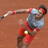 Roger and out: Roger Federer serves to Latvia's Ernests Gulbis during their French Open fourth-round match on Sunday. Gulbis won 6-7 (5-7), 7-6 (7-3), 6-2, 4-6, 6-3. | AFP-JIJI