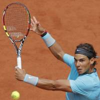 Cruise control: Rafael Nadal plays a shot from Serbia's Dusan Lajovic in their fourth-round match in the French Open on Monday. Nadal won 6-1, 6-2, 6-1. | AP