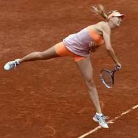 Great escape: Maria Sharapova serves during her French Open quarterfinal win over Garbine Muguruza on Tuesday. | AFP-JIJI