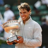 Been here before: Rafael Nadal poses with the trophy after defeating Novak Djokovic 3-6, 7-5, 6-2, 6-4 in the final of the French Open on Sunday in Paris. Nadal won his fifth straight title, and ninth overall, on the clay at Roland Garros. | REUTERS