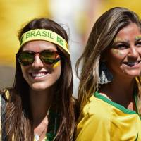 The beautiful game: Brazil supporters wait for the start of their team's match against Chile at the Mineirao stadium in Belo Horizonte, Brazil. Tickets to Brazil's World Cup matches have proven to be out of the price range of many Brazilians. | AFP-JIJI
