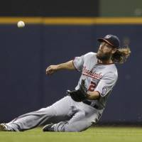 Under control: Washington's Jayson Werth makes a sliding catch during the Nationals' 4-2 win over the Brewers on Tuesday. | AP