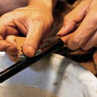 Brothers Shuhei and Ryohei polishing lacquered fishing rods in their workshop. | KIT NAGAMURA
