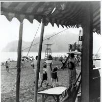 An image from the 1930s, of ladies and children on a beach near Kamakura with Enoshima island in the background. | ARCHIVE OF THE KAMAKURA CITY CENTRAL LIBRARY
