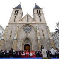 Orthodox Christian priests pray outside Sarajevo Cathedral in the Bosnian capital in September 2012. | AP