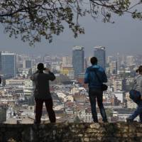 Visitors admire Sarajevo from an elevated part of the city in April. | AP