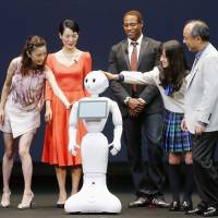 Learning fast: Softbank CEO Masayoshi Son (far right) introduces Pepper, a robot that can recognize emotions. | KYODO