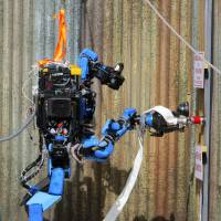 Helping hand: Schaft, a disaster-relief robot, connects a hose to a fire extinguisher. | KYODO