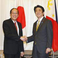 Prime Minister Shinzo Abe and Philippines President Benigno Aquino III shake hands before their summit meeting at the prime minister's residence on Tuesday. | KYODO