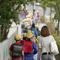 Children in Nikko, Tochigi Prefecture, make their way on Wednesday to Osawa Elementary School, which Yuki Yoshida attended prior to her murder in 2005. Students still walk to the school in groups for safety. | KYODO