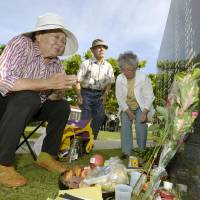 A man who lost a relative during the war in Okinawa prays Monday at the Cornerstone of Peace, a monument listing the names of war victims, at Peace Memorial Park in Itoman, Okinawa Prefecture. | KYODO