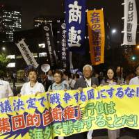 Demonstrators march from Tokyo's Hibiya Park toward the Diet on Tuesday evening, denouncing the ruling Liberal Democratic Party's drive to ease decades-old restraints on the Self-Defense Forces. | KYODO