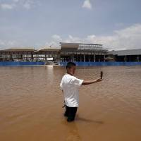 In the wash: A resident stands in a flooded area of Wujiaba airport in Yunnan Province, China earlier this month. As a result of global warming, the wet areas of the world are getting wetter and the dry areas drier, with water conflicts already a reality. | REUTERS