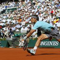 On the grand stage: Rafael Nadal tries to hits a return against Andy Murray during their French Open semifinal on Friday. Nadal defeated Murray 6-3, 6-2, 6-1. | AFP-JIJI