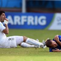 A lot to chew on: Uruguay's Luis Suarez (left) was given a severe suspension by FIFA for biting Italy's Giorgio Chiellini (right) during their match at the World Cup on Tuesday. | AFP-JIJI