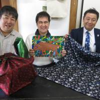 'Furoshiki' wrappers made using Hakata-ori fabric featuring designs by Kosuke Ota (center) are displayed on April 18 in Fukuoka's Minami Ward. Sanui Orimono Co. President Katsuhiko Sanui (right) is a vocal supporter of Ota and his artistic talents. | KYODO