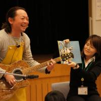 Tetsuya Ando plays guitar during a picture book reading session for fathers and children in Utsunomiya, Tochigi Prefecture, in December 2012.   COURTESY OF TETSUYA ANDO