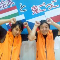 Father and son Yasuo and Takao Hazaki pose June 1 in front of a sign promoting the free outdoor children's game of 'onigokko' as a sport to be enjoyed by all.   TOMOHIRO OSAKI