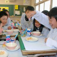 A pupil at Hirai Elementary School in the town of Miki, Kagawa Prefecture, pours rare-sugar syrup onto his lunch. Miki is where mass production of rare sugars first took place. | KYODO