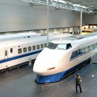 Bullet train generations — the 0 series at right, the 100 series in the middle and the 300 series — are displayed at the SCMAGLEV and Railway Park in Minato Ward, Nagoya, on Feb. 16. | KYODO