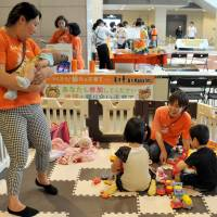 Two care providers look after children while their parents participate in an event sponsored by AsMama Inc. at Queens Square Yokohama on June 7. | YOSHIAKI MIURA