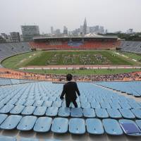 Hundreds of volunteers form the words 'Tokyo 2020' at National Stadium in Shibuya Ward, Tokyo, on May 25 to promote the 2020 Olympic Games. The stadium served as the main venue for the 1964 Olympics. | AP