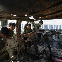 Children look inside a burned-out vehicle following a raid by security forces on an al-Qaida hideout in Yemen last Tuesday. The attack in the Arhab region left five militants and six personnel dead. | AP