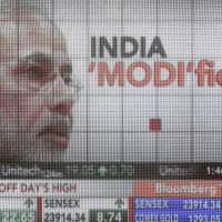 A large screen projects coverage of now-Prime Minister Narendra Modi during India's general election in Mumbai on May 16. | BLOOMBERG