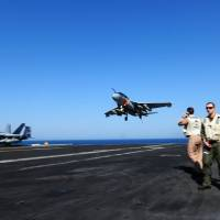 An EA-6B Prowler lands on the aircraft carrier USS George H.W. Bush on Thursday in the Persian Gulf, in a photo released by the U.S. Navy. The warship was directed to remain within reach of Iraq following rapid gains there by Islamists. | AFP-JIJI
