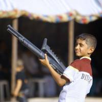 An Iraqi boy holds a weapon Tuesday as he takes part in a gathering of Shiite tribesmen showing their willingness to join Iraqi security forces in the fight against ISIS militants who have taken over several cities in the country's north. | AFP-JIJI