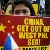 A protester displays a placard during a demonstration against Beijing's claim to areas of the South China Sea, at the Chinese Consulate in Manila on Thursday. | AFP-JIJI