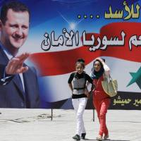 A pair of girls walk in front of a campaign billboard for Syrian leader Bashar Assad, who was expected to dominate Tuesday's presidential election. This billboard bears the slogan 'Yes for Assad . . . Yes for a secure Syria.' | AFP-JIJI