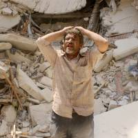 A man stands in front of the remains of a building bombed by Syrian regime forces in the northern city of Aleppo on Monday, a day ahead of the nation's presidential vote, which the opposition has labeled a sham. | AFP-JIJI