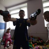 Children of families who fled fighting in the Ukrainian city of Slovyansk play with toy guns at a dormitory for displaced people in the town of Ilovaisk on Tuesday. Some residents of nearby Luhansk say they want to flee the fighting but have nowhere to go. | REUTERS