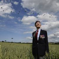 British parachute veteran Fred Glover, 88, who took part in a glider-borne D-Day attack on a German artillery battery in Merville, northern France, in 1944, watches as 300 multinational troops drop from the sky at Ranville on Thursday. Veterans on Friday attended ceremonies along the Normandy coast marking 70 years since the landings, which historians say turned the tide of the war. | REUTERS