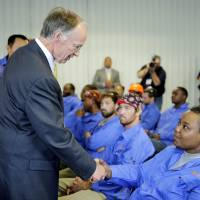 Alabama Gov. Robert Bentley and Golden Dragon Copper U.S.A. Chairman Changjie Li (left) meet Golden Dragon employees before the company's grand opening ceremony in Pine Hill on May 28, in this photo provided by the governor's office. | AP