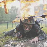 A Chinese paramilitary member crawls under fire obstacles during a drill at a base in Chaohu, Anhui province, on May 5.   REUTERS