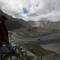 A sheep herder looks out at the open-pit Antamina mine in San Marcos, Peru, above disputed property from which the mine is trying to evict him. Twenty years ago, the rugged, mineral-rich Andean nation went out of its way to attract multinational mining companies, and became Latin America's undisputed economic growth leader, but it also has experienced devastating side effects. | AP