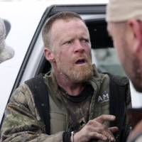 Detectives place fugitive Troy James Knapp (center) into custody in the mountains outside Ferron, Utah, in April last year. | AP