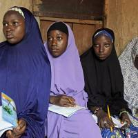 Maimuna Abdullahi (left) listens during class as she and others attend school in Kaduna, Nigeria, on June 2. Maimuna is one of thousands of divorced girls in Nigeria who were married as children and then got thrown out by their husbands or simply fled. | AP