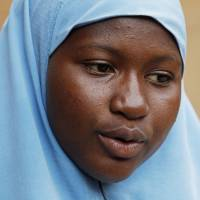 Maimuna Abdullahi sits outside her school in Kaduna, Nigeria, on June 1. Her body bore the scars of an abused woman all over: a swollen face, a starved body and, barely a year after her wedding, a divorce. But for Maimuna, it all happened before she was 14. | AP