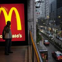 A man waits outside a McDonald's outlet in central Hong Kong. McDonald's global sales at established restaurants grew 2.5 percent in Asia, the company said Monday. | AP